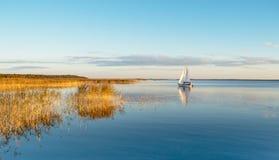 Bateau à voile sur un lac calme avec la réflexion Photos stock