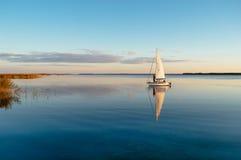 Bateau à voile sur un lac calme avec la réflexion Photos libres de droits