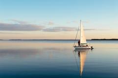 Bateau à voile sur un lac calme avec la réflexion Photo libre de droits
