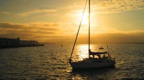 Bateau à voiles au coucher du soleil Images stock