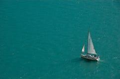 Bateau à voiles d'isolement sur un fond bleu de lac Photo libre de droits