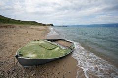 Bateau abandonné sur le sable, côte de lac Baikal, Olkhon. Photo libre de droits
