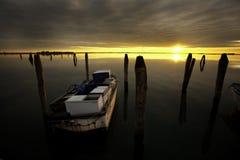 Bateau accouplé sur l'eau calme au coucher du soleil Photo libre de droits