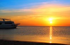 Bateau au point d'attache et lever de soleil au-dessus de mer Photographie stock libre de droits
