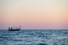 Bateau avec des pêcheurs en mer Photo stock