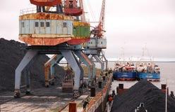 Bateau avec du charbon au port fluvial de Kolyma Images stock