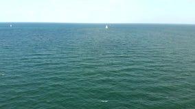 Bateau avec une voile blanche flottant sur les hautes mers banque de vidéos