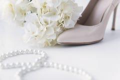 Bateau blanc de pantoufle avec l'épingle à cheveux, fleurs blanches d'hortensia, collier de perle, perles photo libre de droits