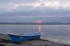 Bateau bleu au rivage de lac au coucher du soleil Images stock