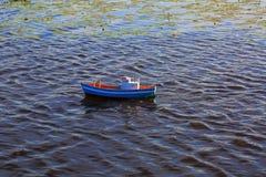 Bateau bleu commandé par radio mignon de jouet sur la surface de l'eau L'eau et nénuphars foncés de lac sur le fond Concept de pa Photo libre de droits