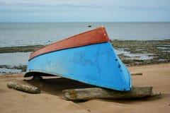 Bateau bleu-rouge inversé sur la plage Photographie stock