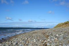 Bateau-citerne avec les nuages bleus au-dessus de la plage beal rocheuse Images libres de droits