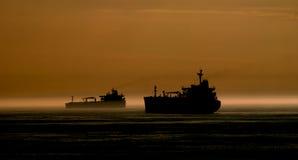 Bateau-citerne de silhouette à l'ancre au coucher du soleil photos libres de droits