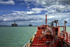 Bateau-citerne manouvered près de la plateforme pétrolière images libres de droits