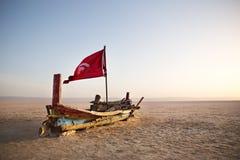 Bateau coloré abandonné dans le désert à l'aube Images libres de droits