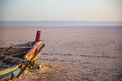Bateau coloré abandonné dans le désert à l'aube Image libre de droits