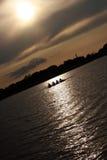 Bateau d'aviron de gens au coucher du soleil Photos libres de droits