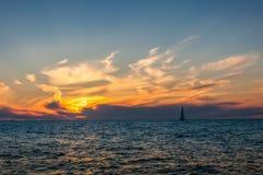 Bateau dans le coucher du soleil de mer Photographie stock libre de droits