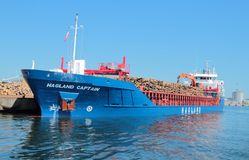 Bateau dans le port chargé avec des rondins Photo stock