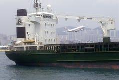 Bateau de cargo dans Hong Kong Harbor et l'avion de passagers au décollage Photo libre de droits