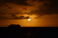 Bateau de croisière silhouetté contre le ciel de coucher du soleil Images stock
