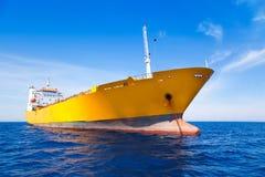 Bateau de jaune de cargaison de point d'attache en mer bleue Images stock