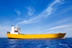 Bateau de jaune de cargaison de point d'attache en mer bleue Photographie stock