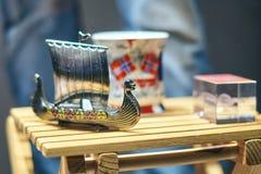 Bateau de jouet de Viking en métal également connu sous le nom de karve ou knarr et tasse norvégienne traditionnelle avec le drap images stock