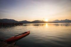 Bateau de kayak sur le lac avec la belle scène de coucher du soleil Photos stock