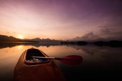 Bateau de kayak sur le lac avec la belle scène de coucher du soleil Image stock