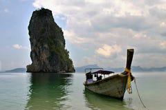 bateau de Long-arrière et la roche Images stock