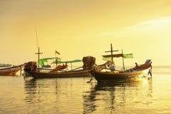 Bateau de longue queue de tradition en mer sur le coucher du soleil d'or. image libre de droits