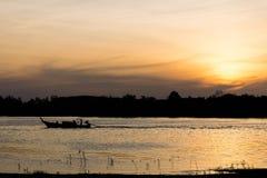 Bateau de longue queue en mer au coucher du soleil Photographie stock