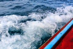Bateau de longue queue se déplaçant mer éclaboussant l'eau cassant le wa images stock
