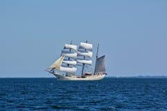 Bateau de navigation blanc gréé en carré en mer avec un rivage éloigné à l'arrière-plan Photo libre de droits