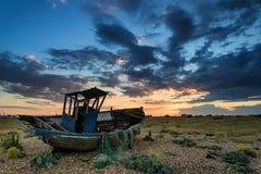Bateau de pêche abandonné sur le paysage de plage au coucher du soleil Image stock