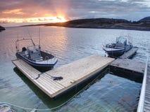 Bateau de pêche avec les cannes à pêche flottant au rivage, égalisant la mer colorée Images libres de droits