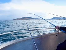 Bateau de pêche avec les cannes à pêche flottant en mer ouverte Beau ciel de fond Pêche sportive Images libres de droits