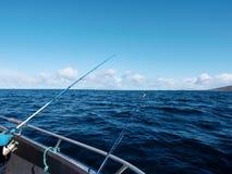 Bateau de pêche avec les cannes à pêche flottant en mer ouverte Beau ciel de fond Pêche sportive Photos libres de droits