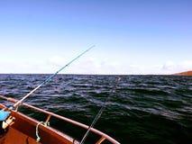 Bateau de pêche avec les cannes à pêche flottant en mer ouverte Beau ciel de fond Pêche sportive Photographie stock libre de droits