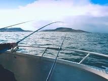 Bateau de pêche avec les cannes à pêche flottant en mer ouverte Beau ciel de fond Pêche sportive Photos stock