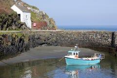 Bateau de pêche bleu dans un port abrité Photos libres de droits