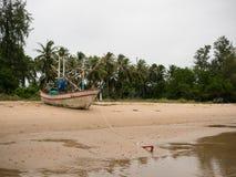 Bateau de pêche de calmar sur la plage pendant le jour nuageux de matin, avec le fond d'arbre de noix de coco Photographie stock libre de droits