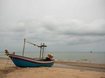 Bateau de pêche de calmar sur la plage pendant le jour nuageux de matin, avec le fond de mer Images stock