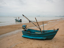 Bateau de pêche de calmar de vert bleu sur la plage pendant le jour nuageux de matin, avec le fond de mer Photographie stock