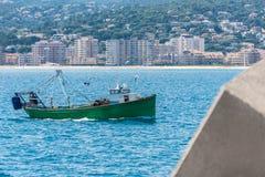 Bateau de pêche de chalutier entouré par des mouettes retournant au port photo stock
