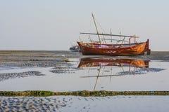 Bateau de pêche d'été à la plage et réflexion dans l'eau Image libre de droits