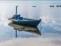 Bateau de pêche dans l'eau avec la réflexion Photographie stock libre de droits