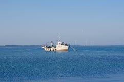 Bateau de pêche dans l'estuaire à l'arrière-plan des turbines de vent Image stock