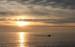Bateau de pêche dans le coucher du soleil Photographie stock
